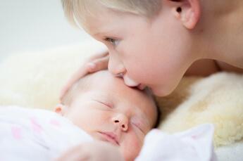 Der größere Bruder küsst zärtlich seine schlafende Schwesetr