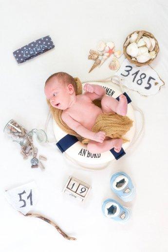 Maritimes Babyfoto: Neugeborenes liegt in Rettungsring, um ihn herum diverse Gegenstände, die Auskunft über Gewicht, Länge, Geburtsdatum geben