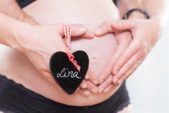 Die Elternhände formen ein Herz auf dem Schwangerschaftsbauch. Am Daumen hängt ein Namensschild