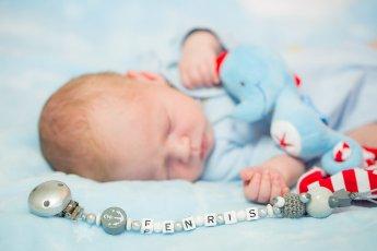 Neugeborener Jung schläft und hält einen blauen Stoffdrachen fest, vor ihm liegt ein namenskettchen auf das der Babyfotograf den Fokus gelegt hat
