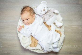 Aus der Vogelperspektive fotografiertes Baby, das mit weißem Teddy in einem kleinen Körbchen liegt