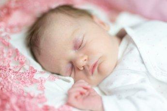 Portrait eines schlafenden Babys mit rosa Deckchen und unscharfem Hintergrund