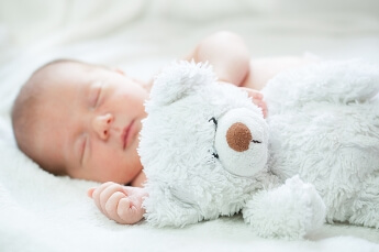 Nacktes Baby in weißer Umgebung mit weißem Teddy auf den die Schärfe des Fotos liegt