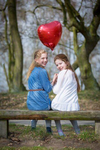 Zwei Freundinnen auf einer Parkbank blicken über die Schulter zum Fotograf