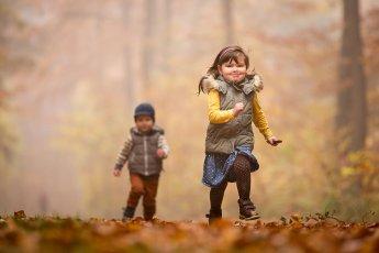 Bruder und Schwester beim Wettlauf im Herbstwald