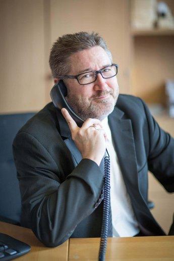 Unternehmer mit sympathischen Lächeln beim Telefonieren fotografiert
