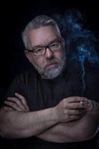 Charakterstarkes dunkles Porträt eines grau melierten Mannes mit Zigarette