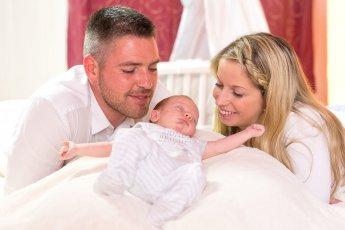 Glückliches Elternpaar beugt sich von links und rechts über das in der Mitte liegende Baby im hell ausgeleuchteten Babyzimmer