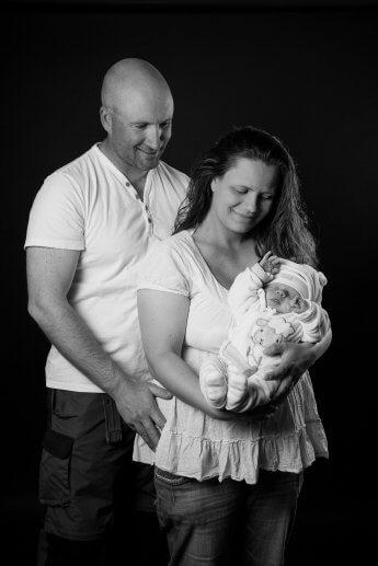 Schwarzweiss-Studioaufname eines jungen Elternpaars mit Baby