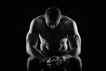 Bodybuilder im Dunkeln mit leichter Lichtsilhouette