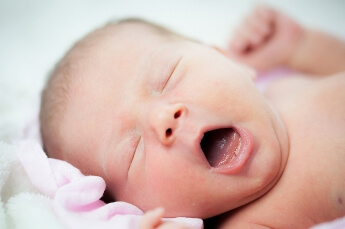 Mit einer Tageslichtlampe ausgeleuchtet: gähnendes Baby