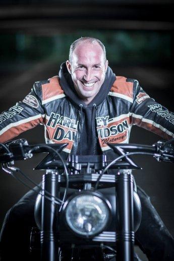 Beim Fotografieren in einer Tiefgarage lacht ein Motorradfahrer von seinem Zweirad in die Kamera