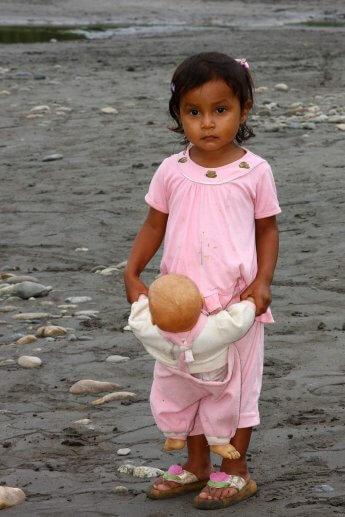 Ein kleines Mädchen mit Puppe am Flussufer, welches ich vor einigen Jahren in Ecuador fotografierte