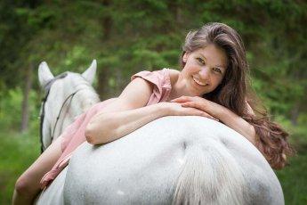 Hübsche junge Dame liegt auf ihrem Pferd und lächelt in die Kamera