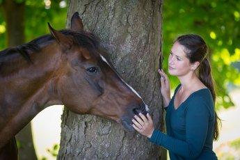 Portraitfoto von Pferd und Reiterin an einem Baumstamm