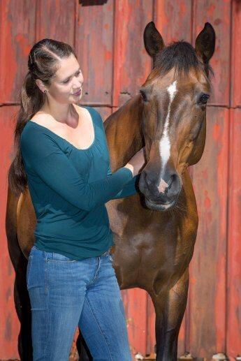 Reiterin blickt bei Sonnenschein auf ihr Pferd, beide stehen vor der rotbraunen Wand des Pferdestalls