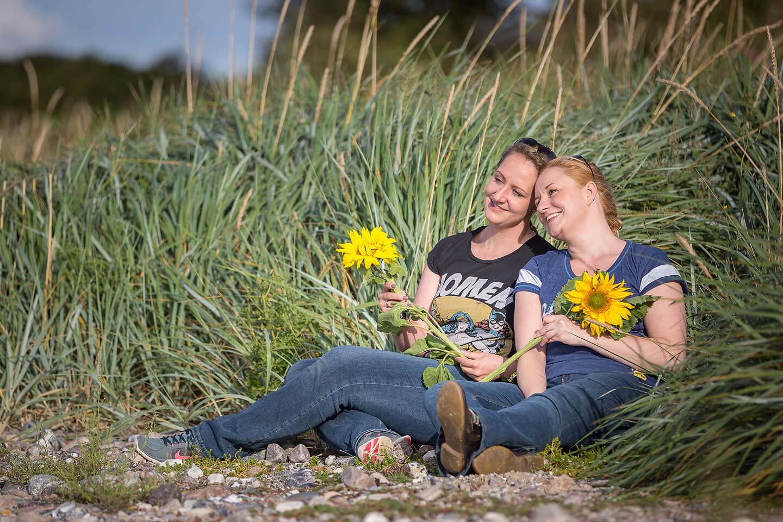 Zwei Schwestern liegen in hohem Gras und halten eine Sonnenblume in der Hand