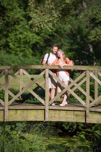 Pärchen auf Holzbrücke blickt in die Ferne und wird vom Sonnenlicht beschienen
