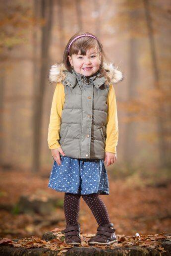 Mädchen im Kindergartenalter beim Fotoshooting im Herbstwald