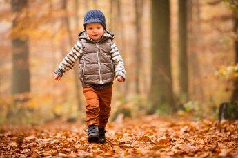 Kleiner Junge im Herbstwald