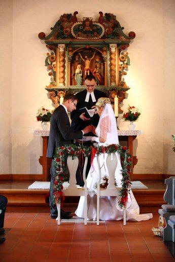 Das Brautpaar steckt sich die Ringe vor dem Altar auf
