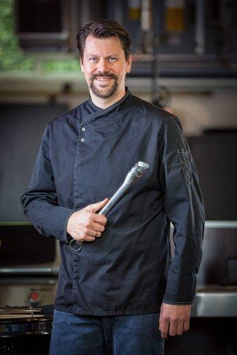 Koch mit Grillzange von mehreren Blitzgeräten ausgeleuchtet
