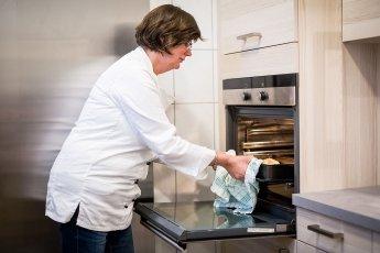 Die Köchin nimmt den Kuchen aus dem Ofen