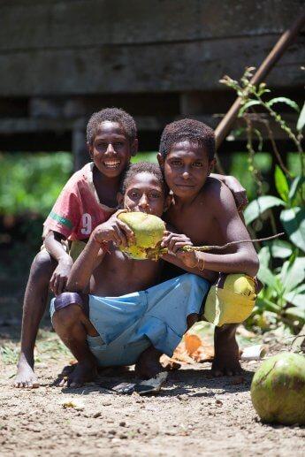 Drei Kinder posieren mit Kokosnuss für die Kamera