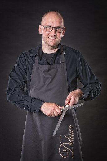 Portraitfoto – schwarz gekleideter Koch mit Messer und Abziehstahl vor schwarzem Studiohintergrund