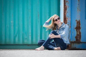 Model hockt beim Fotoshooting barfüssig vor einem Container dem Boden und fährt sich durchs Haar
