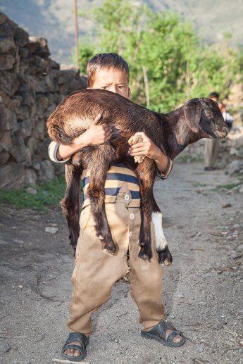Kind aus einem Dorf an der nepalesischen Grenze präsentiert der Kamera stolz eine Ziege