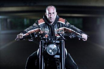 Harleyfahrer auf seinem Bike sitzend mit ernstem Blick in die Kamera