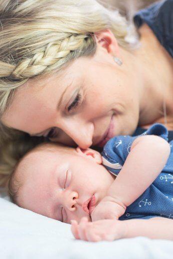 Homeshooting bei Mama und Baby, die blau gekleidet auf dem Bett liegen