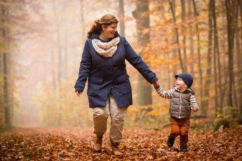Mutter mit kleinem Sohn Hand in Hand im herbstlichen Wald fotografiert
