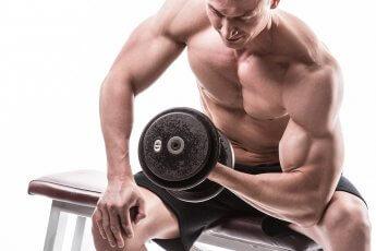 Bodybuilder mit Hantel auf Trainingsbank sitzend im Studio vor weißem Hintergrund fotografiert