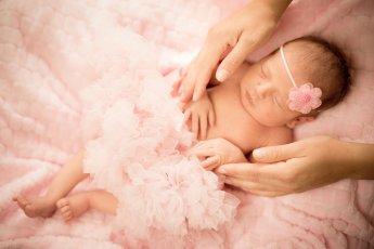 Newbornshooting eines neugeborenen Mädchens mit Kopfschleife und Tütü
