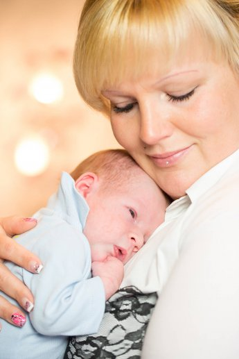 Junge blonde Mutter drückt ihr Neugeborenes an sich und hält die Augen geschlossen