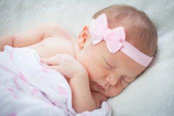 Friedlich schläft das Baby mit seiner rosa Kopfschleife beim Newborn-Shooting