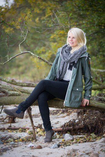 Junge blonde Dame sitzt beim Shooting auf einem Baumstamm und blickt in die Ferne
