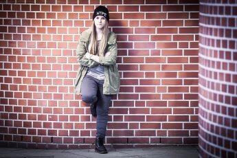 Jugendliche cool an Backsteinmauer gelehnt bei einem Outdoorshooting