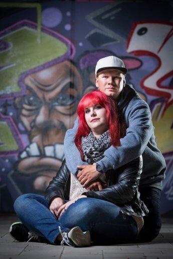 Szene-Pärchen hockt umschlungen vor Graffitti-Wand