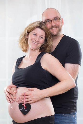 Fotografie von werdenden Eltern vor weißem Hintergrund