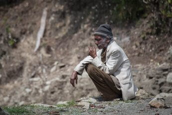 Dünner, alter Mann hockt rauchend in steiniger Umgebung am Boden
