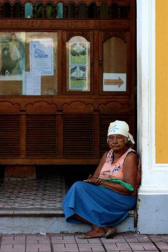 Ältere Dame mit Kopftuch hockt am Eingang einer Kirche und blickt direkt in die Linse des Fotografen