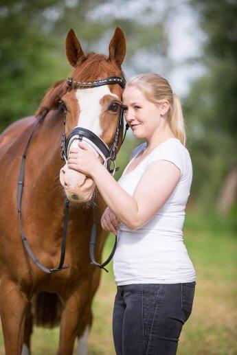 Portraitfoto von junger Frau, die ihren Kopf an den des Pferdes lehnt