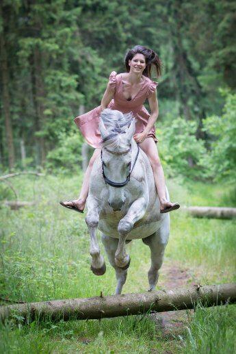 Junge Reiterin in rosefarbenen Kleid springt im Wald mit ihrem Schimmel über einen umgestürzten Baum