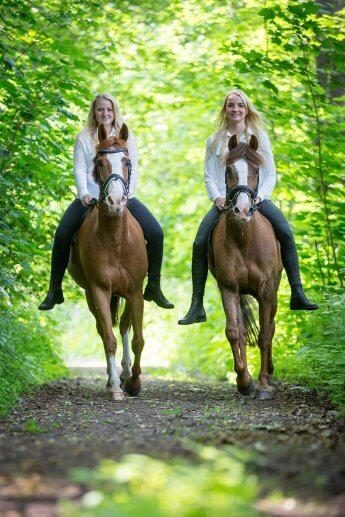 Zwei blonde Schwestern beim Ausritt im Wald aus niedriger Perspektive auf den Auslöser gedrückt