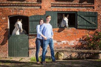 Junges Paar steht vor altem Stallgebäude aus dem zwei Schimmel herausschauen