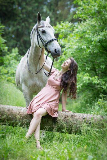 Mit langer Brennweite aufgenommen: Reiterin hockt auf Baumstamm, hinter ihr steht ihr Pferd