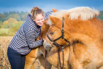 Emotionales Bild: Pferd blickt über die Schulter nach hinten zu der neben ihm stehenden Reiterin